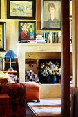 Collection of paintings in living room of old country house - modern paintings above open fireplace on wall painted yellow