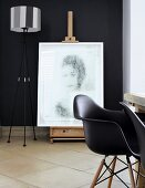 Modern portrait on antique easel against black wall with black Charles Eames chairs in foreground