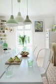 Pendant lamps in various shades of green above freshly baked cakes on white dining table