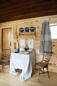 Pale wooden dining room with set table under sloping roof