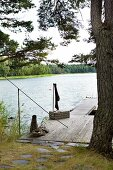 Path paved with stone slabs leading to simple wooden jetty on idyllic lake