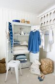 Blue and white items of clothing hanging on door of open wardrobe surrounded by baskets, laundry bag and white metal stool