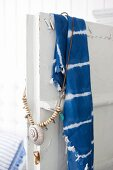 Blue and white batik cloth and necklace with shell pendant hanging over door of vintage cupboard