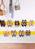 Yellow dado rail used as shoe rack