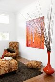 Interior in warm, earthy shades - bamboo-leaf pattern on beige upholstery next to brick red vase