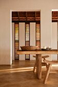Carved wooden table and stools with shutters in beach house retreat, Indian state of Goa