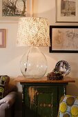 Lamp with clear glass balloon base and small Christmas arrangement of fir cones on vintage cabinet below pictures on wall