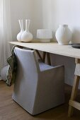 Chair with a gray slipcover at a simple work desk and white vases in assorted styles