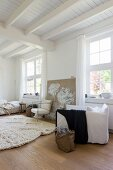 A bag on the floor next to a white upholstered armchair in a simple living room with a white wooden ceiling