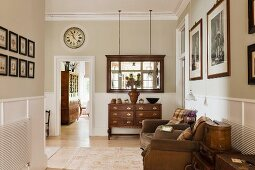 Traditionelle Diele mit antiker Schubladenkommode, gerahmtem Spiegel, bequeme Vintage-Sessel und mit Blick in das Esszimmer