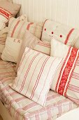 A variety of vintage white, pink and red striped and monogrammed cushion covers by Starched and Crumpled.