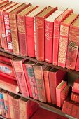 A wooden shelf with three rows of vintage red books