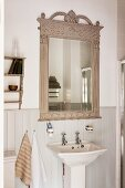 French style wooden mirror frame with carved details and flower bouquet above a wash basin
