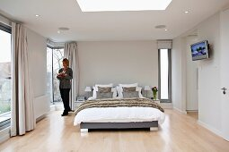 Woman standing next to a bed in an elegant bedroom with floor to ceiling windows