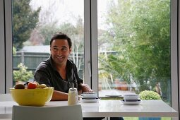 Man having a coffee break at a modern table in front of terrace windows