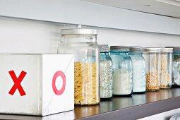 Screw top jars with dry goods on a shelf