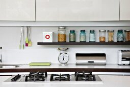 View over the top of a gas stove of a countertop and shelf with screw top jars