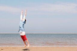 Lady doing gymnastics on the beach