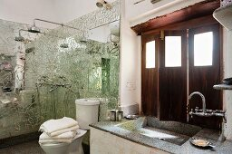 Washstand below window with interior wooden shutters and shower area with mirrored mosaic wall panels