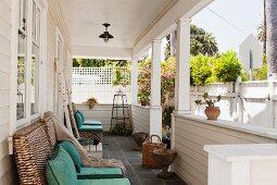 Überdachte Veranda mit weißer Holzverkleidung und Holzsäulen mit Blick über den weißen Gartenzaun