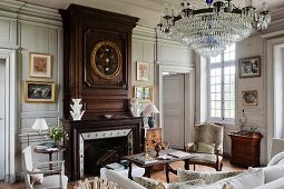 Crystal chandelier above lounge area and fireplace with wood-panelled chimney breast in grand living room