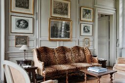 Antique sofa with leopard-skin cover in front of pale, wood-panelled wall and gilt-framed artworks