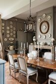 Candlesticks on wooden table and pale, upholstered chairs in grand dining room with wall plates on grey-painted, wood-panelled walls