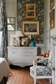 Corner of traditional bedroom with chest of drawers painted pale grey and gilt-framed pictures on wall with wallpapered inserts