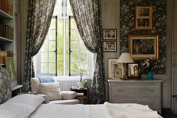 Bed next to draped curtains at lattice window in traditional bedroom