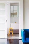 Armchair with blue cover in front of doorway with open sliding door and view of yellow stool in front of washstand