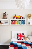 Teenager's bed with Union Flag scatter cushion below wall-mounted shelving modules