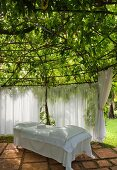 Secluded area in garden - daybed with white covers on terracotta tiled floor and curtains below tree canopy with spider web of struts