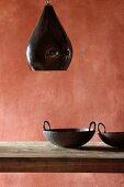 Black pendant lamp above wooden table in dining room with brick red wall