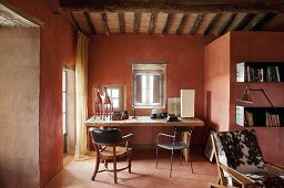 Rustic wooden table in corner of Mediterranean living room with brick red walls