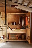 Suitcases, clothing and textiles in wooden wardrobe on castors