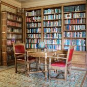 Historic library with antique table and chairs in front of a built in bookcase wall unit