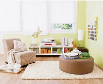 Gepolsterter Bodentisch auf Teppich und Sessel in grün getöntem Wohnzimmer
