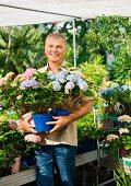 Älterer Mann steht mit Topfblumen in einem Gartencenter