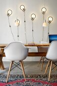 Bauhaus shell chairs at rustic wooden table in front of modern scone lamps