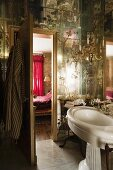 Sconce lamps and pedestal sink in ensuite bathroom with mirrored ceiling and walls