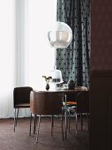60s-style dining set with brown wooden shell chairs below spherical pendant lamp in front of window with black and white patterned curtain