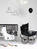 White Bauhaus rocking chair and black, vintage-style pram next to cot with bars painted black and white