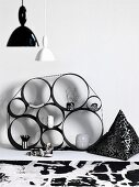 Shelves made from metal rings of various sizes bound together against wall and vintage pendant lamps with black and white lampshades