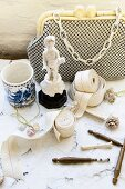 Rolls of trim next to ornament and vintage beaded evening bag on lace tablecloth