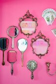 Collection of mirrors and hand mirrors on pink wall