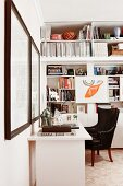 Corner office area - black leather armchair at white desk and fitted shelving