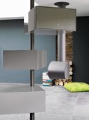 Designer interior with grey storage boxes on metal pole and modern fireplace in background