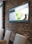 Horizontal, rectangular fixed window with petrol-coloured frame in stone-tiled wall in designer house