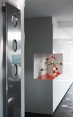 White, glossy, fitted cupboards with cut-out corner and orange shelf holding crocheted, floral ornament