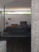 Designer bed suspended from ceiling by metal poles below circumferential ribbon window in bedroom with dark parquet floor; pebble mosaic tiled wall in foreground